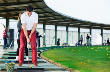 Man preparing to hit ball at golf course