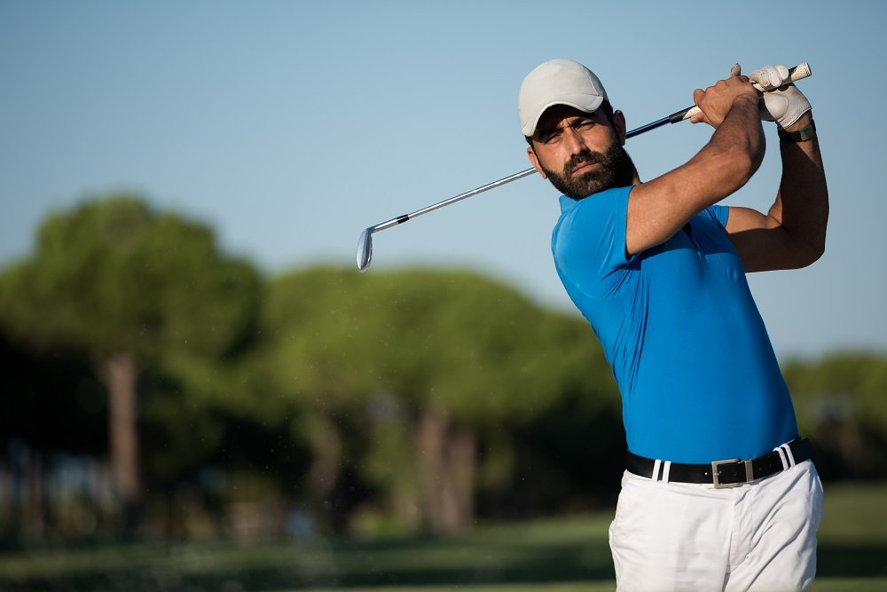pro golfer hitting a sand shot