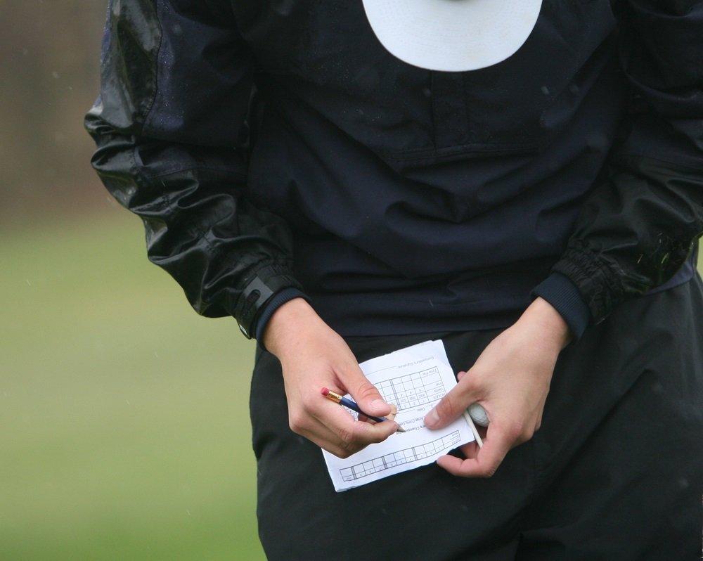 A golfer writes down