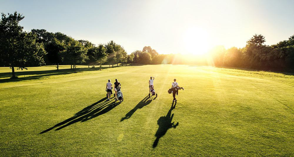 people playing golf in the sun