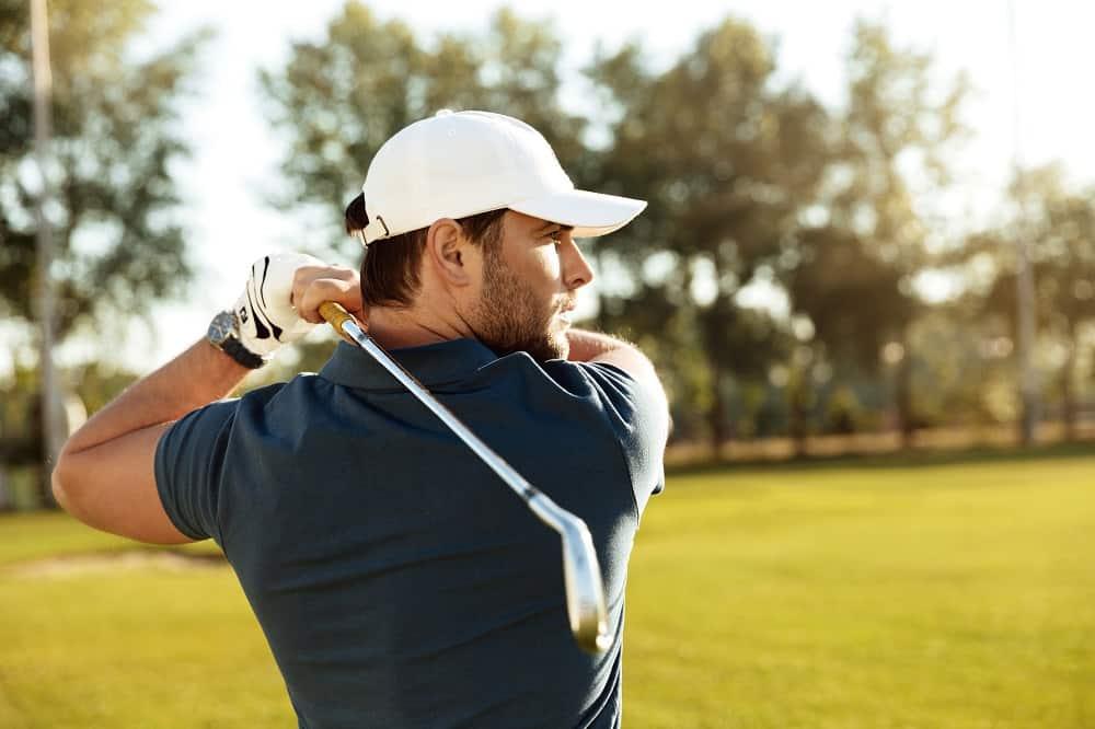 young man shooting golf ball